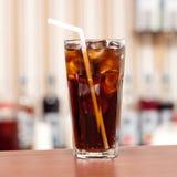 Verre de kola avec de la glace sur la barre Image libre de droits