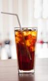 Verre de kola avec de la glace sur la barre Photos stock