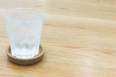 Verre de l'eau avec de la glace sur le bois Photographie stock libre de droits