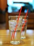 Verre de l'eau avec la paille rouge sur la table en bois Photo stock