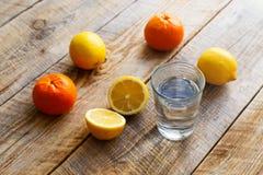 Verre de l'eau avec le citron et les oranges sur la table en bois Photos libres de droits
