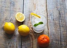 Verre de l'eau avec le citron et les oranges sur la table en bois Image stock