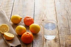 Verre de l'eau avec le citron et les oranges sur la table en bois Photo libre de droits
