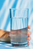 Verre de l'eau dans la main un enfant Photo stock