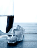 Verre de l'eau et de glaçons de fonte sur une table en bois Photo stock