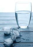 Verre de l'eau et de glaçons de fonte sur une table en bois Photo libre de droits