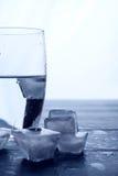 Verre de l'eau et de glaçons de fonte sur une table en bois Image stock
