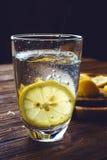 Verre de l'eau minérale pure avec le citron sur la table en bois Photo libre de droits