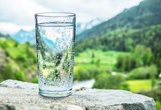 Verre de l'eau sur la pierre Dessus brouillés de montagnes de neige et forêts vertes au fond photo libre de droits