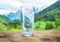 Verre de l'eau sur la pierre Dessus brouillés de montagnes de neige et forêts vertes au fond photo stock