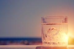 Verre de l'eau sur le fond du beau coucher du soleil Foyer sélectif Images libres de droits