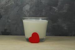 Verre de lait avec le coeur rouge Photographie stock