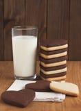 Verre de lait et de biscuits en forme de coeur Photos stock