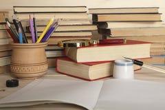 Verre de loupe, crayons colorés dans une tasse en bois, carnet, rétro stylo avec le stylo et vieil encrier encastré de porcelaine Photographie stock