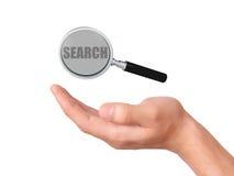 Verre de loupe de prise de main avec le texte de recherche Images stock