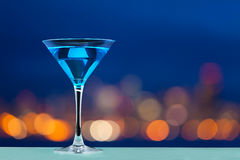 Verre de martini se tenant contre des lumières de ville Photographie stock
