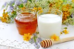 Verre de miel de lait et de fleur dans un pot Image libre de droits