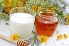 Verre de miel de lait et de fleur dans un pot Photographie stock