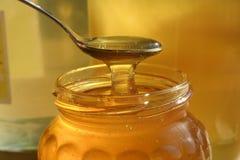 Verre de miel liquide photos stock