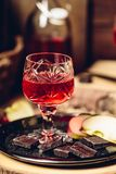 Verre de nalivka fait maison de groseille rouge avec les tranches et le chocolat de pomme photographie stock libre de droits