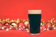 Verre de pinte de Nonik de bière foncée ou de bière anglaise vaillante avec les babioles et la tresse de lumières de Noël sur le  photos libres de droits