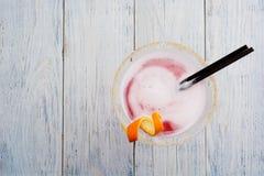 Verre de plan rapproché de cocktail cosmopolite décoré de l'orange sur le fond en bois de barre Photographie stock libre de droits