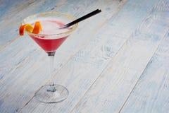Verre de plan rapproché de cocktail cosmopolite décoré de l'orange sur le fond en bois de barre avec l'espace de copie Photographie stock