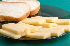 Verre de plat avec des tranches de fromage sec et de pain blanc Image stock