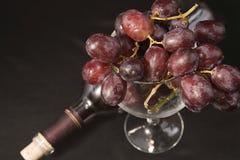 Verre de raisins avec la bouteille de vin Photo stock