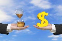 Verre de symbole dollar et d'heure avec deux mains Photo stock