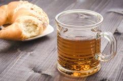 Verre de thé avec le croissant/verre de thé avec le croissant sur un fond en bois foncé Foyer sélectif photo libre de droits