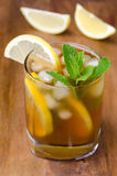 Verre de thé de glace avec le citron et la menthe sur un fond en bois Photo libre de droits