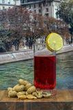 Verre de vermouth avec des arachides sur une table en bois photographie stock