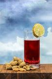 Verre de vermouth avec des arachides sur une table en bois image libre de droits