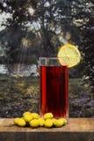 Verre de vermouth avec des olives sur une table en bois photographie stock libre de droits