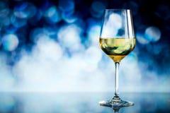 Verre de vin blanc contre un bokeh rougeoyant - copiez l'espace, choisi photographie stock