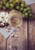 Verre de vin blanc, de raisins, de noix de cajou et de fromage à pâte molle image libre de droits