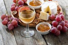 Verre de vin blanc et de casse-croûte froids sur une table en bois Image stock