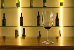 Verre de vin contre la rangée de bouteilles image libre de droits
