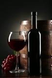 Verre de vin rouge avec la bouteille et baril sur le fond noir Photos libres de droits