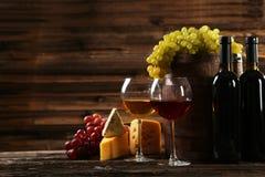Verre de vin rouge et blanc, de fromages et de raisins sur le fond en bois brun Photographie stock
