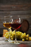 Verre de vin rouge et blanc, de fromages et de raisins sur le fond en bois gris Photographie stock libre de droits
