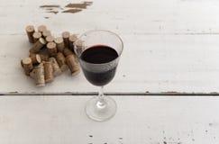 Verre de vin rouge et pile des lièges Photos stock