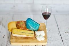 Verre de vin rouge et variation de fromage sur le conseil en bois photographie stock