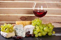 Verre de vin rouge, servi avec des raisins et le fromage photo libre de droits