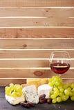 Verre de vin rouge, servi avec des raisins et le fromage images stock