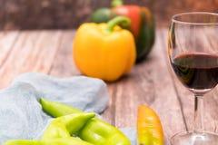 Verre de vin rouge sur la table en bois avec les milieux jaunes et verts de paprika avec l'espace de copie Images libres de droits