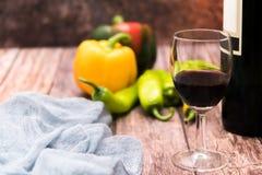Verre de vin rouge sur la table en bois avec les milieux jaunes et verts de paprika avec l'espace de copie Image stock