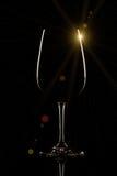 Verre de vin sur le fond noir avec la fusée du soleil photographie stock