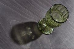 Verre de vin vert en cristal vide avec un modèle, sur un fond en bois foncé Photographie stock